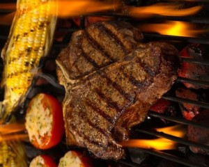 Tbone on grill with tomato and corn